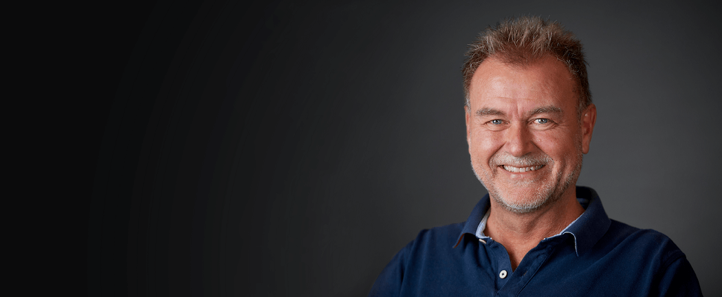 Nærrevisions revisionsekspert i blå polo smiler foran sort baggrund