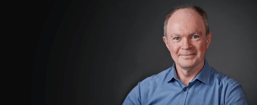Erfaren revisor hos Nærrevision i blå skjorte med sort baggrund