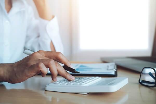 Nærrevision revisor ved skrivebord med hånden på en hvid regnemaskine og papirblok foran hende